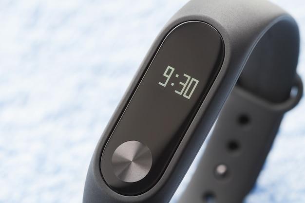 Black fitness watch (activity tracker) on the blue textile surface. closeup, selective focus Premium Photo