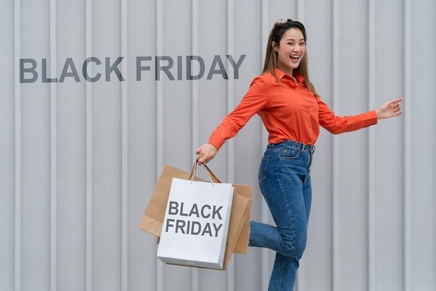 검은 금요일 개념, 쇼핑 과정에서 상점 근처에 다채로운 쇼핑 가방과 함께 걷는 많은 쇼핑 가방을 들고 여자 프리미엄 사진
