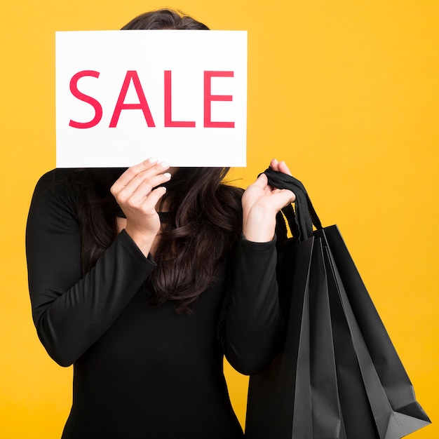 Black friday model covering her face with a sale banner Premium Photo