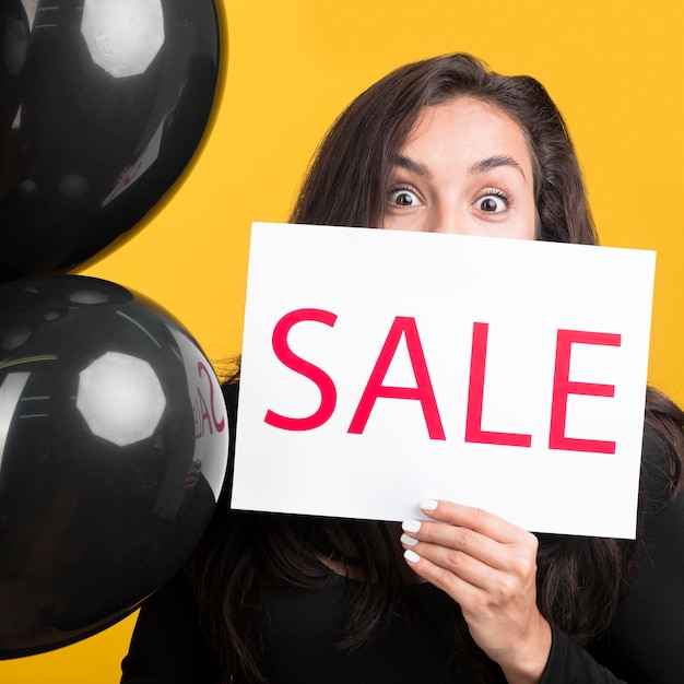 Black friday model holding sale banner and balloons Premium Photo