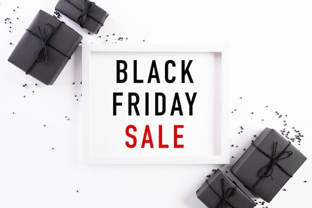 Black friday sale banner text on white picture frame with black gift box. Premium Photo