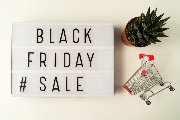 Black friday sale text on light board with plant Free Photo