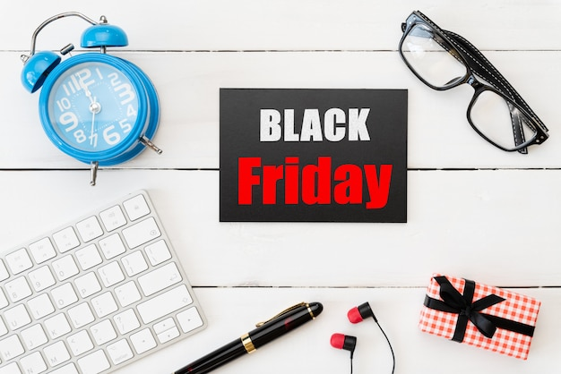 Black friday sale with gift box, glasses, pen and alarm clock on wooden table Premium Photo