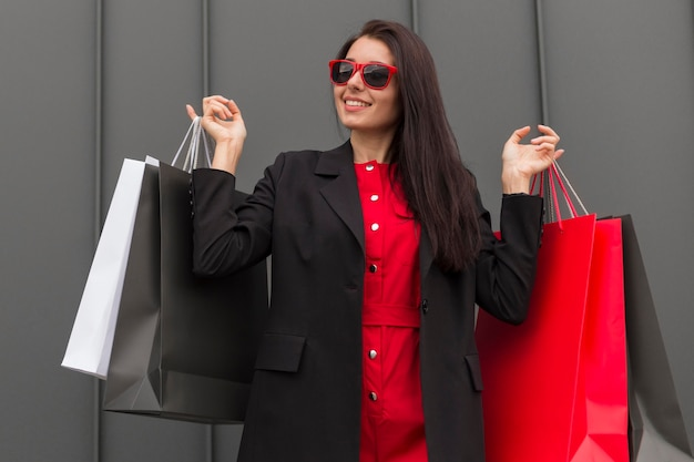 様々な買い物袋を保持している黒い金曜日販売女性 無料写真