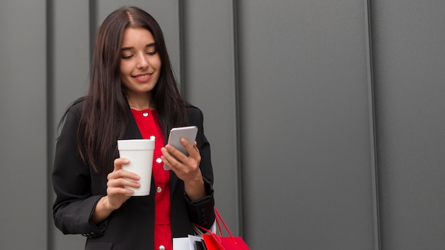 Donna di vendita venerdì nero con caffè e telefono cellulare Foto Gratuite