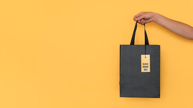 Black friday shopping bag on yellow copy space background Free Photo