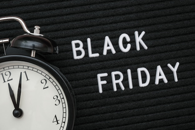 Black friday text on black letterboard and alarm clock Premium Photo