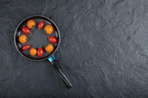 チェリートマトがたっぷり入った黒いフライパン。高品質の写真 無料写真