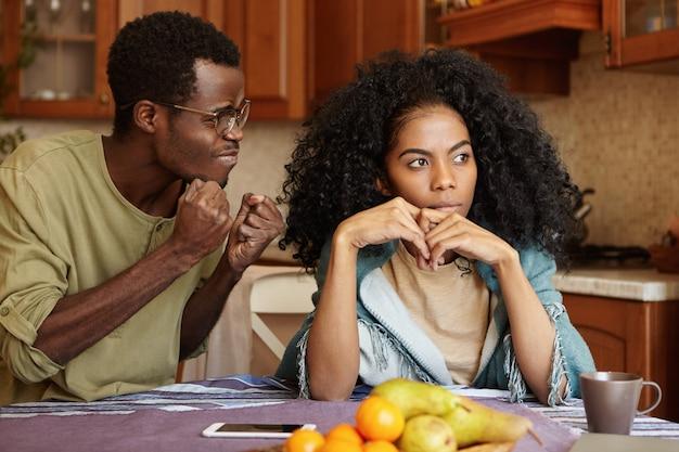 無関心な妻に怒り狂った拳で腹を立てる怒りに満ちた黒。台所のテーブルで深刻な喧嘩を持っているアフリカのカップル 無料写真