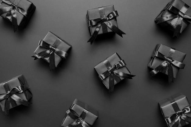 Disposizione di regali neri su sfondo nero Foto Gratuite
