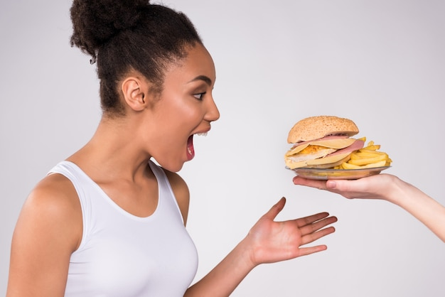 Black girl is glad about cheeseburger. Premium Photo