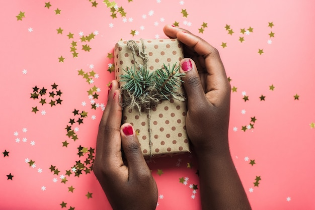 Black girl is holding a gift of kraft paper Premium Photo