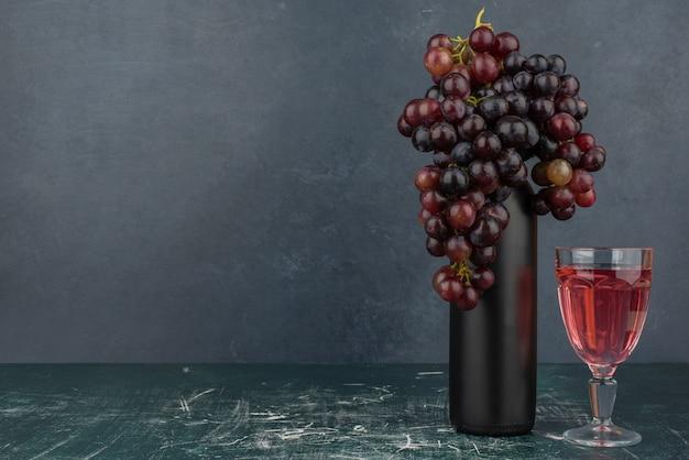 大理石のテーブルの上のボトルとグラスワインの周りの黒ブドウ 無料写真