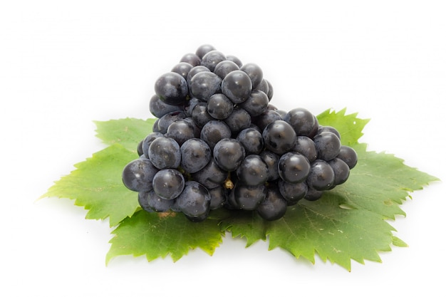 Black grapes bunch isolated on white background with green leaf package design element Premium Photo
