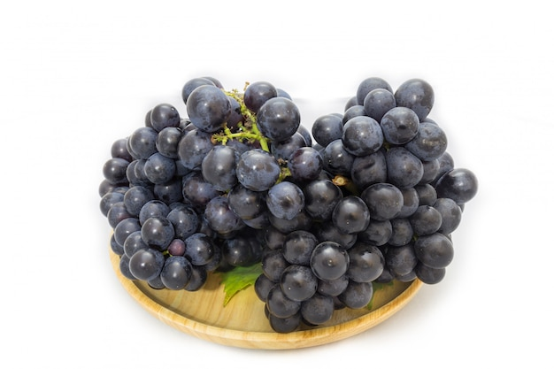 Black grapes bunch isolated on wooden plate and white background with green leaf package Premium Photo