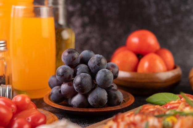 トマトと木の板に黒ブドウオレンジジュースとピザ。 無料写真