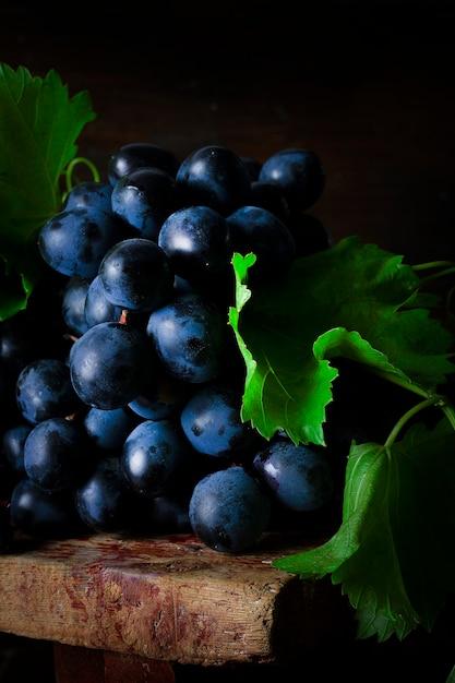 Черный виноград с листьями, деревенский, вид сверху Premium Фотографии