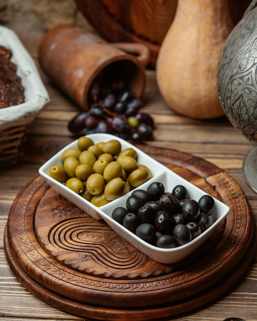 Black and green marinated olives in white bowl. Free Photo