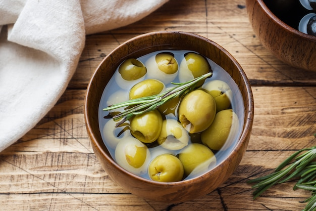 Black and green olives in wooden bowls on wooden table Premium Photo
