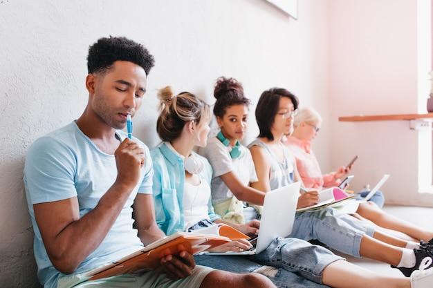 難しいテストで理解しようとしている青いシャツを着た黒人の男。ノートパソコンを持って床に座って友達を見て、何かを話しているスタイリッシュな女子学生。 無料写真