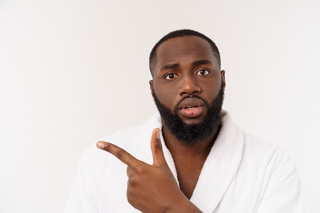 Black guy wearing a bathrobe pointing finger with surprise and happy emotion. Premium Photo