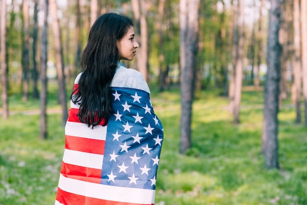 Black-haired female wrapped in flag of usa Free Photo