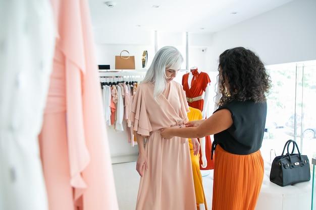 Assistente di negozio dai capelli neri che aiuta la donna a provare il nuovo vestito e la regolazione della cintura. cliente che sceglie i vestiti nel negozio di moda. acquisto di vestiti nel concetto di boutique Foto Gratuite