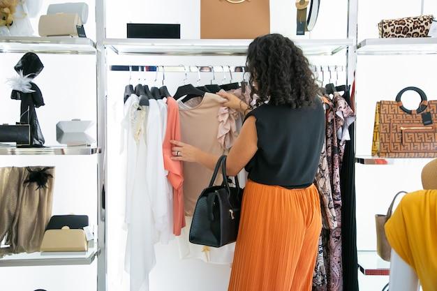 Donna dai capelli neri che sceglie i vestiti e la navigazione di abiti e camicie su rack. vista posteriore. negozio di moda o concetto di vendita al dettaglio Foto Gratuite