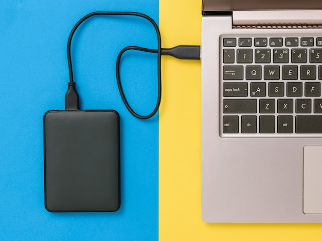 Black hard drive and laptop on yellow and blue background. the view from the top. the concept of backup storage. flat lay. Premium Photo