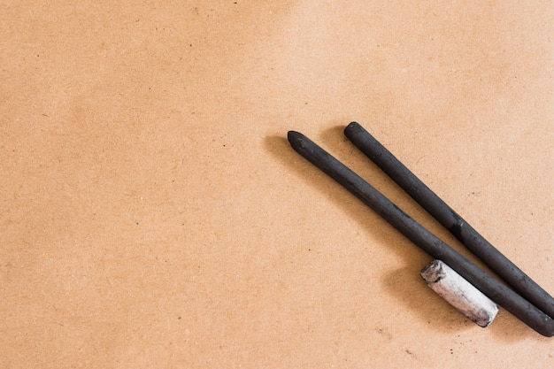 Black hard wood charcoal stick for drawing on plain backdrop Free Photo
