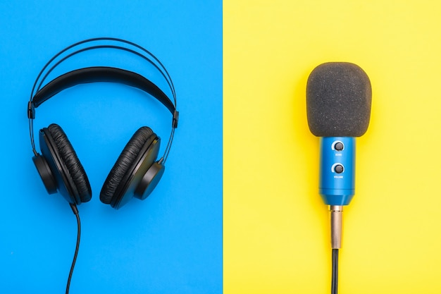 Black headphones and blue microphone on yellow and blue Premium Photo