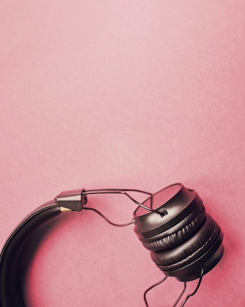 Black headphones on a red background, top view, copyspace. Premium Photo