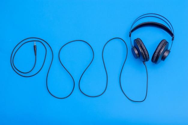 파란색 배경에 파도의 모양에 코드와 함께 검은 헤드폰. 음악 듣기 및 커뮤니케이션을위한 액세서리. 프리미엄 사진
