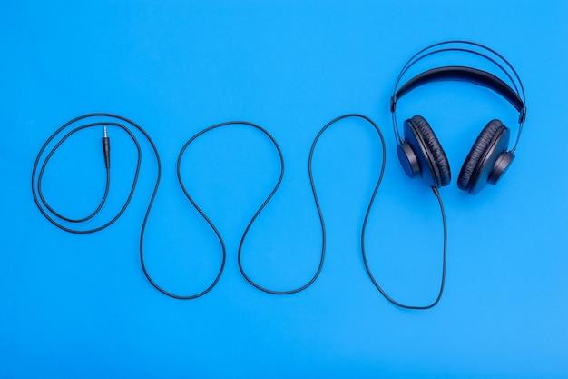 Black headphones with cord in shape of wave on a blue background. accessory for listening to music and communication. Premium Photo