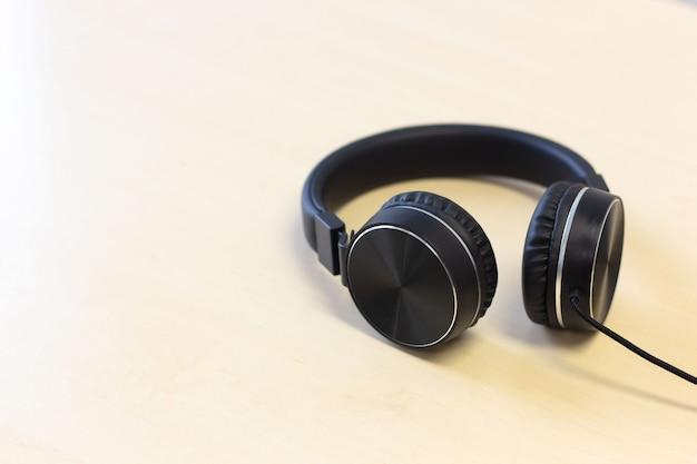 Black headphones on wooden table background Premium Photo