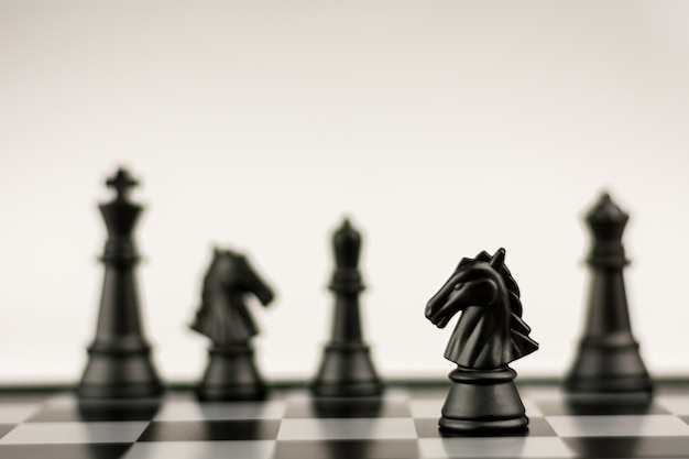 Black horse chess stand alone on a chessboard. - business winner and fight concept. Premium Photo
