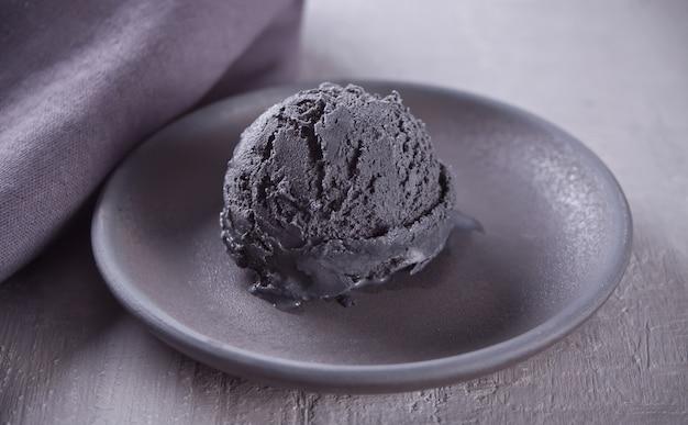 Black ice cream on a black ceramic plate with gray napkin on a gray table Premium Photo
