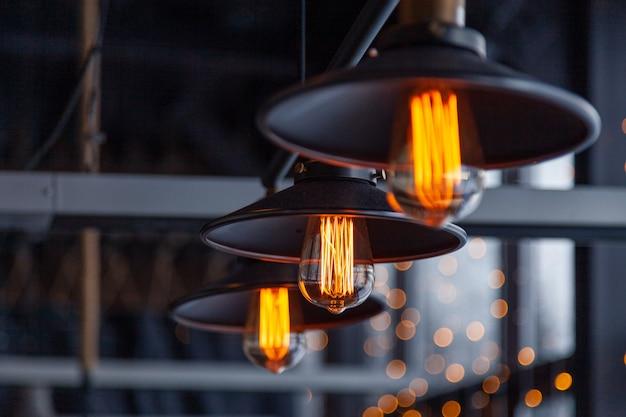 エジソンランプが付いている黒い鉄のロフトシャンデリア Premium写真