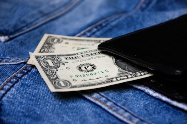 Black leather wallet with money on back blue jeans pocket denim texture. Premium Photo