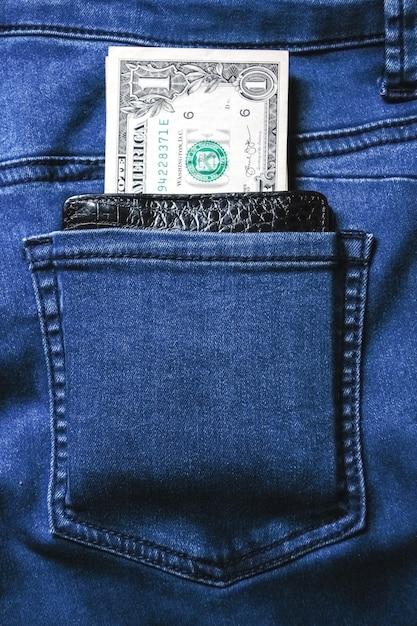 Black leather wallet with money in back blue jeans pocket denim texture. Premium Photo