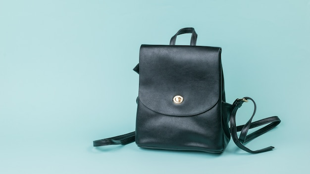 Black leather women's backpack on blue Premium Photo