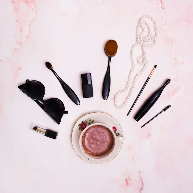 Black lipstick; sunglasses; makeup brush; mascara; white pearl necklace and nail varnish bottle over the ceramic coffee cup Free Photo