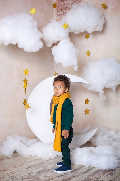 A black little boy in a green sweater and a yellow scarf costs about a month thoughtfully. a little prince. little african american. pensive child. the child has fun and plays in kindergarten. school Premium Photo