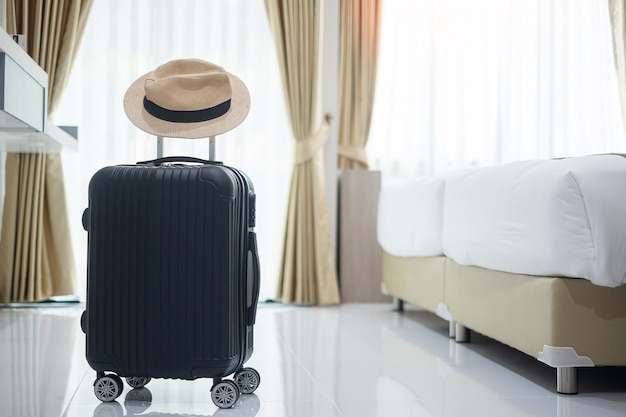 Black luggage and hat in modern hotel room with windows, curtains and bed. time to travel, relaxation, journey, trip and vacation concepts Premium Photo