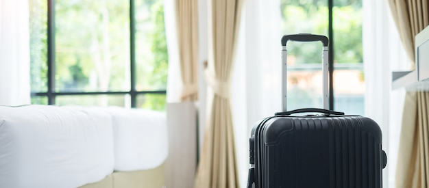 Black luggage in modern hotel room with windows. time to travel, relaxation, journey, trip and vacation concepts Premium Photo