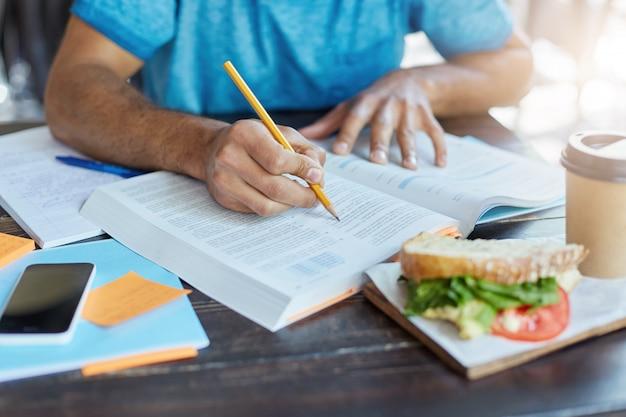 Studente maschio nero che sottolinea informazioni importanti nel libro di testo usando la matita mentre fa ricerche storiche alla mensa universitaria durante il pranzo; telefono, caffè e cibo appoggiati sul tavolo Foto Gratuite