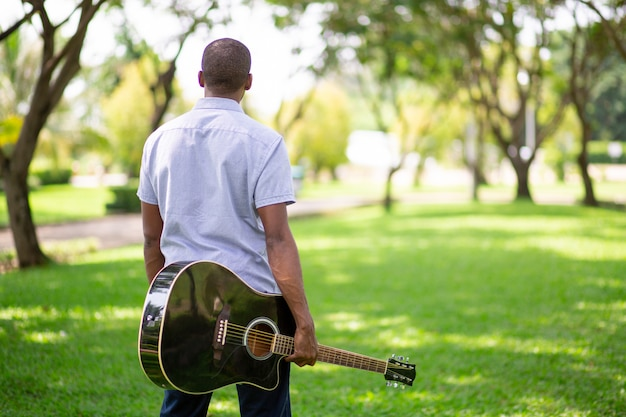 Black man carrying guitar in park Free Photo