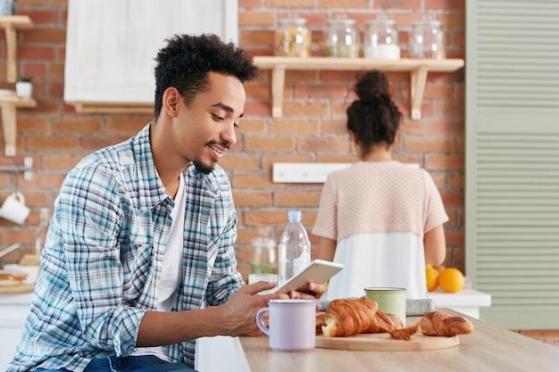 L'uomo nero in abbigliamento casual controlla la posta elettronica o legge le notizie dal mondo su un dispositivo elettronico, beve caffè mattutino e croissant Foto Gratuite