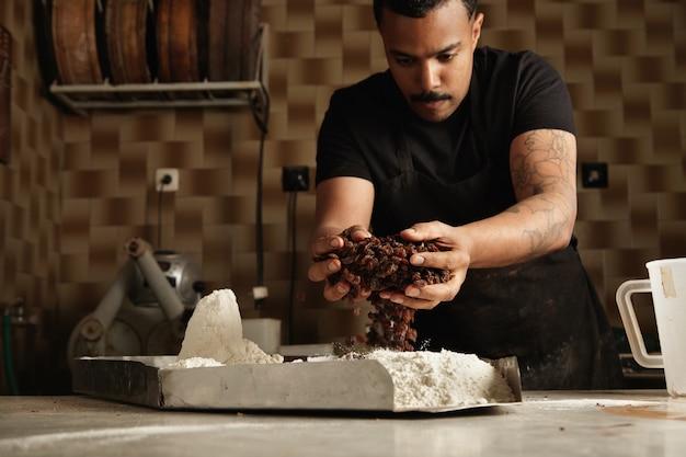 黒人の酋長がケーキを作る。ベイカーは、金属製の鉢の中にドライフルーツを小麦粉に入れて混ぜ合わせ、プロの職人の菓子でケーキ生地を作ります。 無料写真