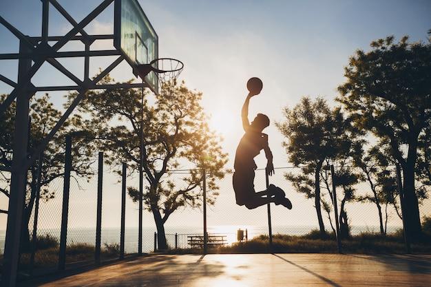 スポーツをして、日の出にバスケットボールをして、シルエットをジャンプの黒人男性 無料写真